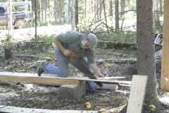 Randy saws out slats or sheathing